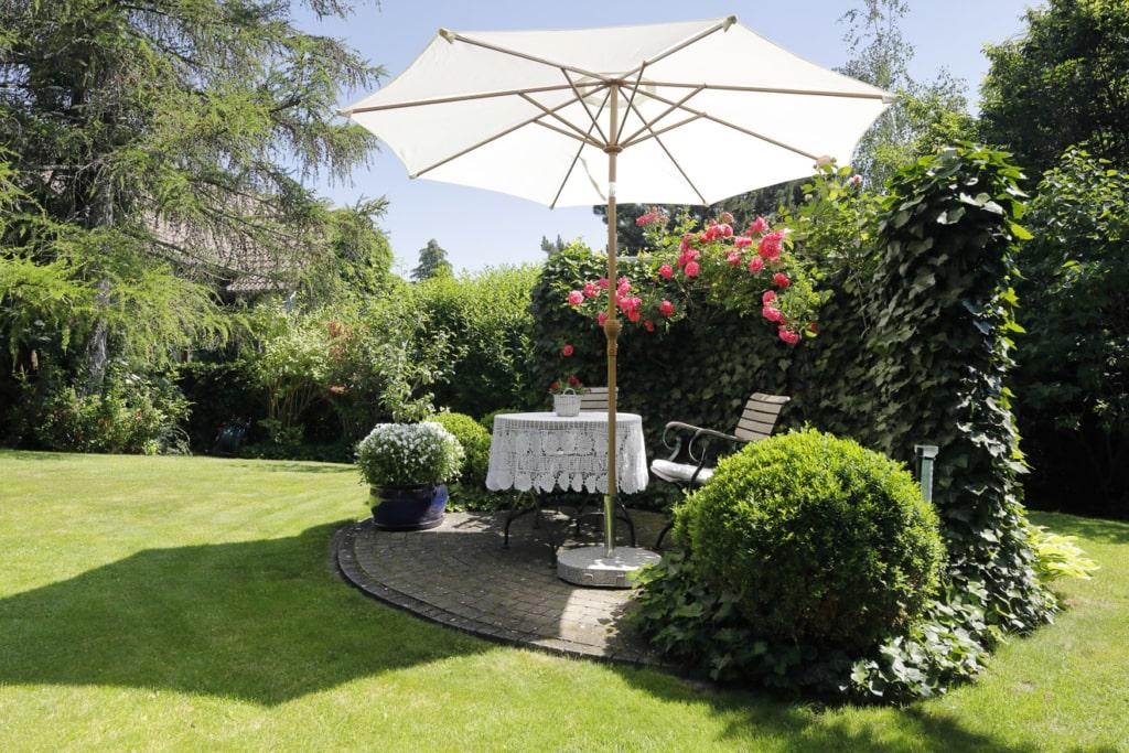 Idyllischer Sitzplatz im Garten mit Sonnenschirm